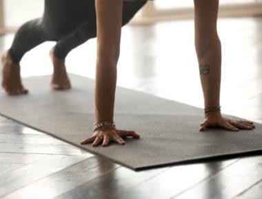 Young sporty yogi woman practicing yoga, doing Push ups or press ups exercise, phalankasana, Plank pose, working out, wearing sportswear, indoor close up, at yoga studio