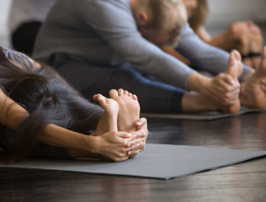 Group of young sporty people practicing yoga lesson with instructor, sitting in paschimottanasana exercise, Seated forward bend pose, working out, students training in club, indoor, studio close up